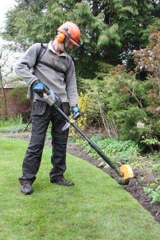 Eco Garden Maintenance (Tadcaster) trimming lawn edges with Pellenc battery powered strimmer