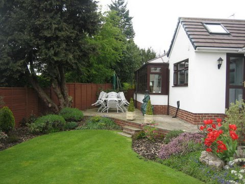 Lawn with patio and boundary trees in the background